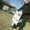 Globe/Roger Nomer<br /> Brian Jones, owner of Jones Heritage, Realtors, put up a sign at a house for sale in Pittsburg on Friday morning.