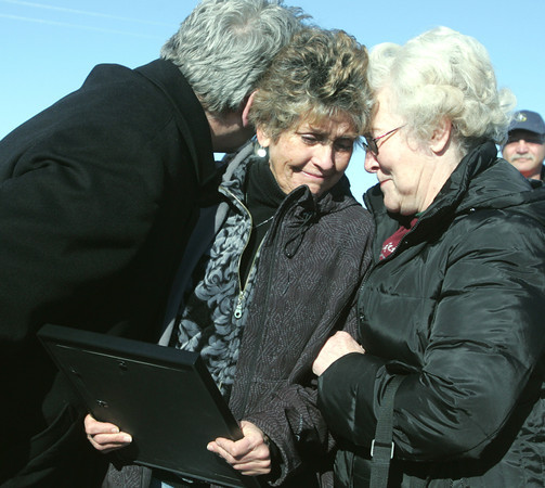 Globe/Roger Nomer<br /> Daniel Wermuth, lead pastor at Joplin Family Worship Center, and Patricia Bryan give Rhonda Wilkins, center, a group hug after she received the deed to land at 2204 S. Grand on Thursday afternoon.