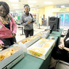 Missouri Southern State University sophomores Shenee Davies, left and Johnnel Creese, center, take advantage of free doughnuts distributed by Campus Activity Board president Elizabeth Means on Tuesday at the Billingsley Student Center.<br /> Globe | Laurie Sisk
