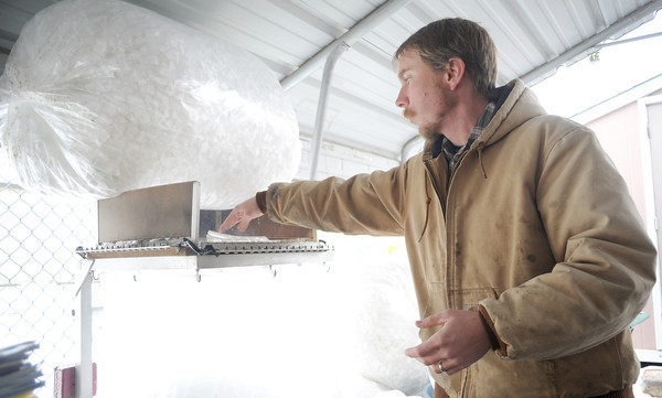 Jonathan Wedge, attendant at the Joplin Recycling Center, melts scraps of styrofoam into cubes to be used for packaging material on Wednesday at the facility.<br /> Globe   Laurie Sisk