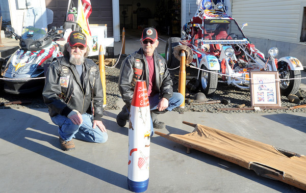 Claire Swatash, left and his brother Duane Swatash kneel next to the veteran's tribute they assembled near Carterville in honor of those who have served.<br /> Globe | Laurie Sisk