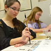 Globe/Roger Nomer<br /> Jasmine Butcher, left, and Hannah Mueller, both freshmen at Thomas Jefferson Independent Day School, practice their form as they write Chinese characters in class on Wednesday.