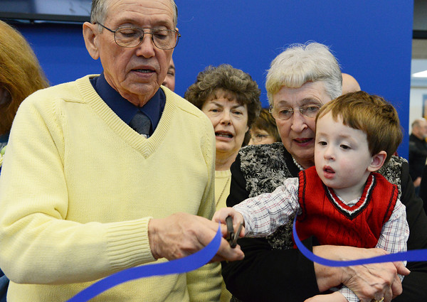 Globe/Roger Nomer<br /> Donors Dwight Ittner, Lanningan, and Judy Duncan, Bella Vista, get help from Duncan's grandson Gale Duncan, 2, as they help a group of donors cut the ribbon on the Crowder College McDonald County Campus on Friday.