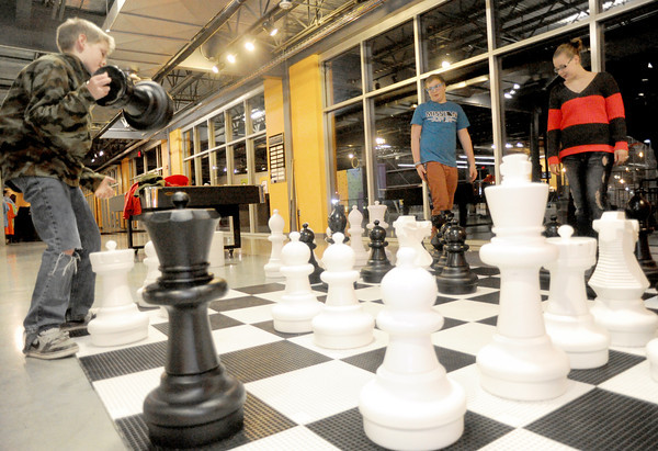 Timothy Pullen, 10, left, challenges his brother, Jotham Pullen, 14, center, to a game of chess as Greta Brauner, 13, observes during family night at the Victory Ministry and Sports Complex on Friday night.