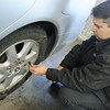 Globe/Roger Nomer<br /> Brandon Spain checks tire pressure on a car at Ivey's Service Center on Friday morning.
