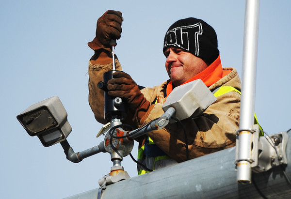 Brian King, an electrical worker with Ewing Signal Construction, works on installing new sensors and cameras Wednesday morning, Jan. 8, 2014, above traffic lights at the intersection of 20th and Main streets.<br /> Globe | T. Rob Brown