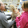 Globe/Roger Nomer<br /> Veterinarian Pamela Helm gets a kiss from Kara, held by Christine Messner, vet tech, during an examine at Main Street Pet Care.