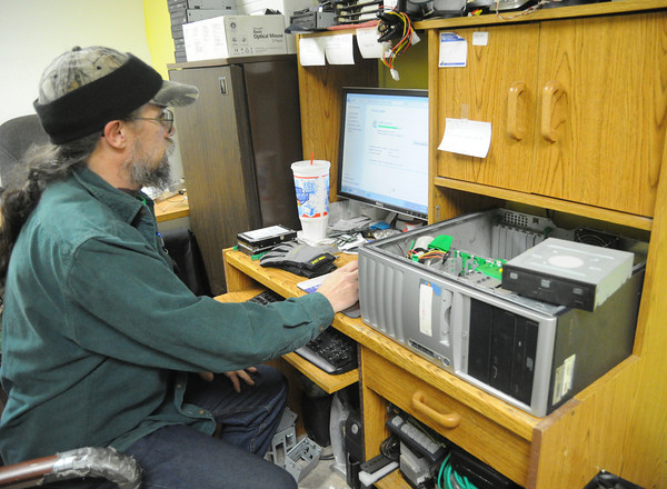 Volunteer Garren Vena inspects electronics for resale at the SEK Recycling Center's electronics store on Thursday. The shop features computers, televisions, stereos and other electronic equipment.<br /> Globe | Laurie Sisk