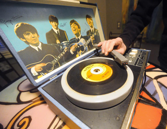 "A copy of the Beatles' hit, ""I want to Hold Your Hand,"" rests on the turntable of Mark Woodin's original Beatles phonograph at his Joplin home.<br /> Globe 
