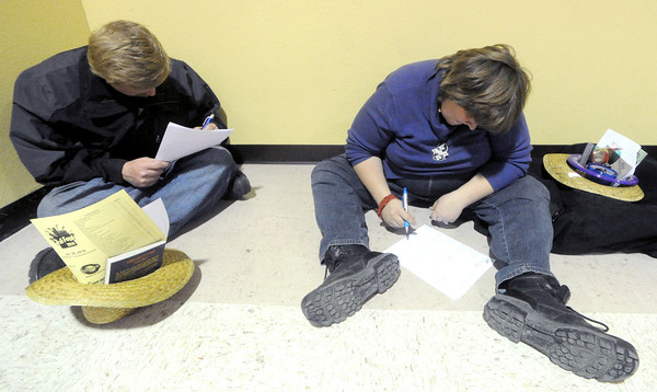 Darrell Wigent, 30, left and Annis Barnes, 24 find a quiet area to fill out employment applications on Tuesday during Job Fair 2014 at the Holiday Inn Convention Center. Hundreds of job seekers met with more than 50 employers during the event.<br /> Globe | Laurie Sisk