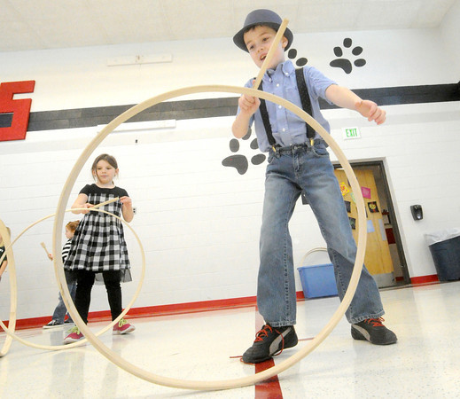 "Carson Mazzocco, 7, tries to master the ""rolling hoop,"" while classmate Chastity Pippins, 7, looks on during a joint celebration of Kansas' birthday and the 100th day of school on Wednesday at Lincoln Elementary in Baxter Springs.<br /> Globe 