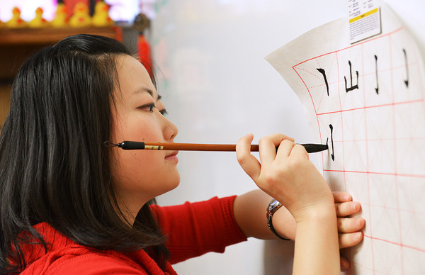 Globe/Roger Nomer<br /> Fei Gao demonstrates a Chinese character for her class at Thomas Jefferson Independent Day School on Wednesday.