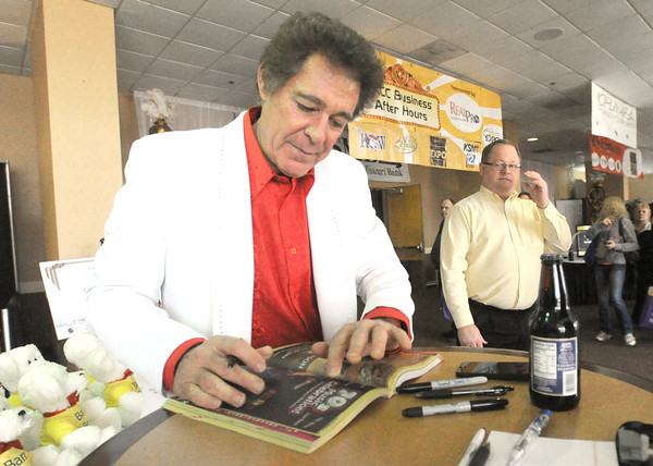 "Actor Barry Williams, best known for his portrayal of Greg Brady on the popular television series, ""The Brady Bunch,"" signs an autograph for Brian Wallace, right on Wednesday afternoon at the Joplin Area Chamber of Commerce Business Expo at the Holiday Inn Convention Center.<br /> Globe 