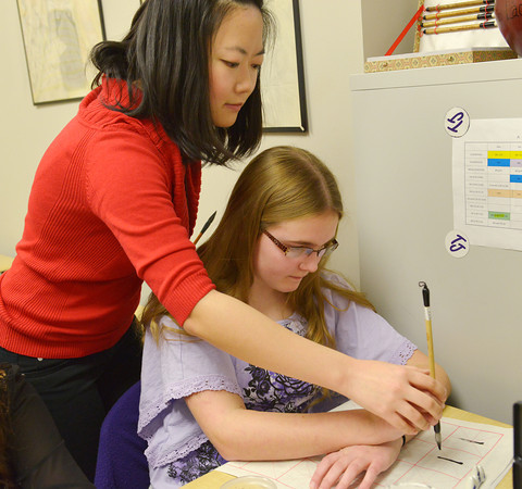 Globe/Roger Nomer<br /> Fei Gao helps Hannah Mueller, a freshman at Thomas Jefferson Independent Day School, with writing a Chinese character on Wednesday.