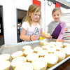 Lincoln Elementary (Baxter Springs) second graders Maddie Hilton, left and Kennedy Goerk receive cupcakes during a joint celebration of Kansas' birthday and the 100th day of school on Wednesday at Lincoln.<br /> Globe | Laurie Sisk