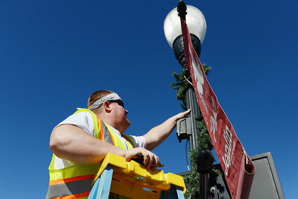 Globe/Roger Nomer<br /> Mark Hendrick, with the City of Joplin sign department, takes down Christmas decorations near Fourth and Main on Monday afternoon.
