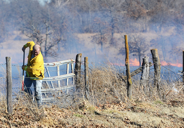 Globe/Roger Nomer<br /> A firefighter clears brush ahead of a fast-moving grass fire near Galena on Sunday afternoon.