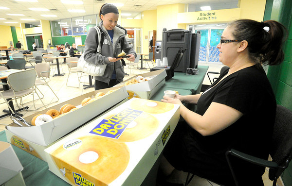 Missouri Southern State University senior Caela Murray, left, receives a free doughnut from Campus Activity Board president Elizabeth Means on Tuesday at the Billingsley Student Center.<br /> Globe | Laurie Sisk