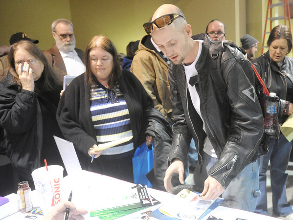 Ciera Karr, 52, center, of Duenweg and Charky Maggard, right, of Springfield inquire about employment opportunities at Total Document Solutions on Tuesday during Job Fair 2014 at the Holiday Inn Convention Center. Hundreds of job seekers met with more than 50 employers during the event.<br /> Globe | Laurie Sisk