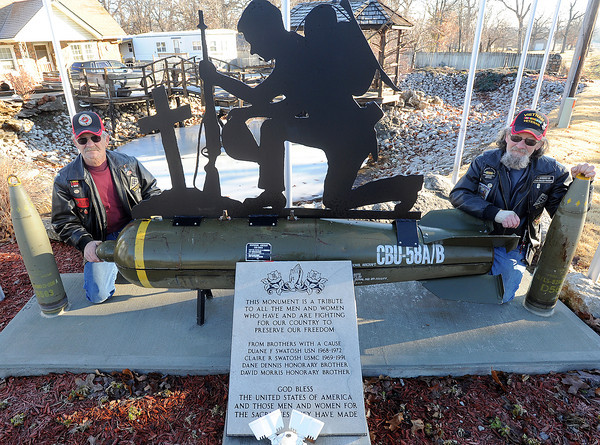 Claire Swatash, left and his brother Duane Swatash kneel next to the veteran's memorial they erected near Carterville in honor of those who have served.<br /> Globe | Laurie Sisk
