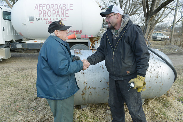 Globe/Roger Nomer<br /> Thomas Spencer, left, talks with Randy Lambeth, of Affordable Propane, while Lambeth fills his propane tank on Thursday.