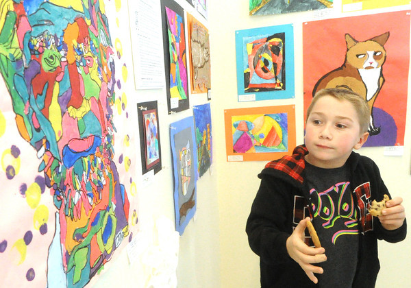 Waylon Lee, 7, Carl Junction looks over a piece by Carterville fourth graders Sophia Coulson, Morgan Bramon and McKenzie Storm during a reception for the Third Annual K-12 Art Show on Saturday at MSSU's Spiva Art Gallery. works from about 150 area students are featured at the exhibit, including a crayon drawing of a lion by Lee. The exhibit opens Monday and runs through Tuesday, January 28.