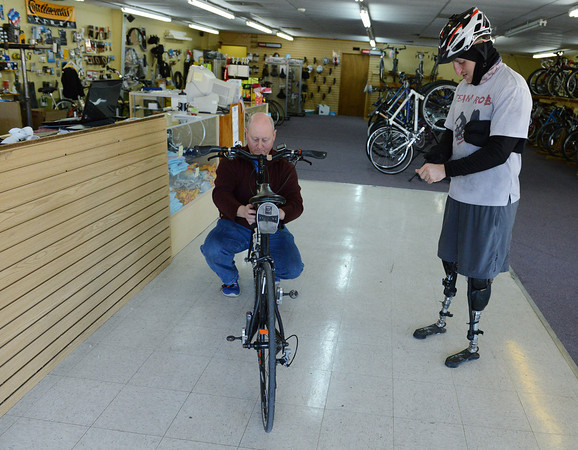 Globe/Roger Nomer<br /> Roger Lomshek, owner of Tailwind Cyclists, checks over Rob Jones' bike during a stop in Pittsburg on Thursday.