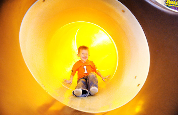 Five-year-old Nolan Houseman of Grove, Okla., slides down playground equipment at Chick-fil-A on  Range Line Road Tuesday afternoon. Houseman was enjoying the warmth of playing indoors.<br /> Globe | Laurie Sisk