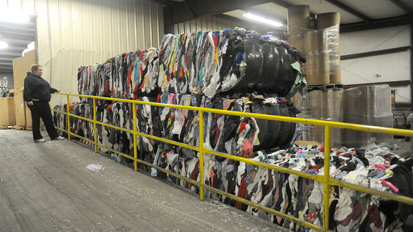 Tausha Ritz, manager of the SEK Recycling Center, looks over the numerous bales of clothing on Thursday at the center.<br /> Globe | Laurie Sisk