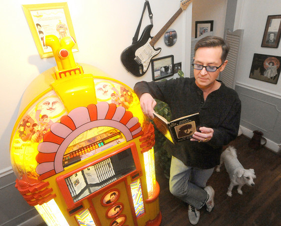 "Lifelong Beatles enthusiast Mark Woodin stands beside his limited edition Yellow Submarine jukebox in his Joplin home while perusing a first edition John Lennon book ""In My Own Write."" Woodin said only about 100 of the jukeboxes were manufactured.<br /> Globe 