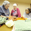 From the left: Anne Foos and Paulette Roberts, both of Webb City, and Margie Wright, of Baxter Springs look over a nearly completed shawl on Saturday at the Webb City Public Library. The three are part of the Hope Through Yarn group that meets the fourth Saturday of each month to create items for charitable organizations. Oraganizer Jill Bresson said the group began about five years ago to make items for soldiers, but has since expanded into making items for hospitals and churches as well.