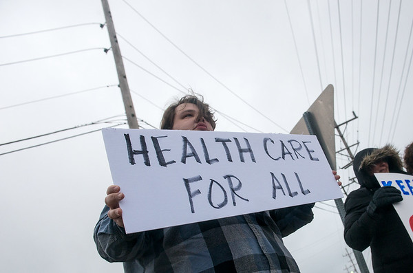 Globe/Roger Nomer<br /> Joshua Lockwood holds a sign in support of the Affordable Care Act during a protest on Tuesday at 32nd and Rangeline.