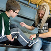 Globe/Roger Nomer<br /> Caroline Capehart places charms that serve as running awards on her son Luke's shoes on Wednesday at Frontenac's Frank Layden Elementary.