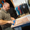 Globe/Roger Nomer<br /> Joe Dillard screen prints a shirt at the All Seasons Outfitters booth on Tuesday at the Joplin Business Expo at Downstream Casino.