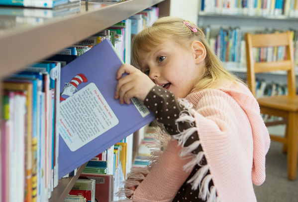Globe/Roger Nomer<br /> Liliana Hanke, 4, Seneca, picks out a book on Thursday at the Seneca Public Library.