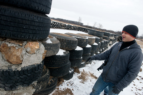 Globe/Roger Nomer<br /> Jimmie Carter talks about using tires for the interior walls of his house near Jasper on Thursday.