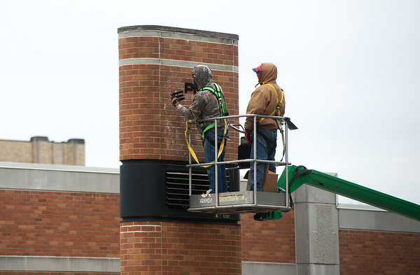 Globe/Roger Nomer Workers remove lettering from the Empire Electric sign on Tuesday in downtown Joplin.