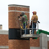 Globe/Roger Nomer<br /> Workers remove lettering from the Empire Electric sign on Tuesday in downtown Joplin.