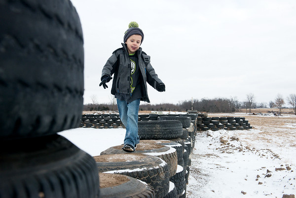 Globe/Roger Nomer<br /> Anderson Carter, 5, runs along the tire walls of his family's house near Jasper on Thursday.