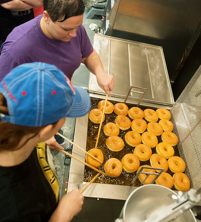 Globe/Roger Nomer<br /> Hollie DeBerry, top, and Sandy Brummett practice cooking donuts on Monday at Hurts Donuts.