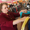 Globe/Roger Nomer<br /> Susan Guthrie arranges clothing at My Sister's Closet on Thursday.