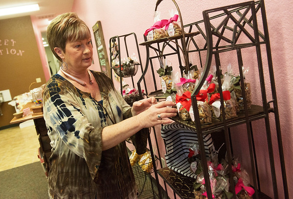 Globe/Roger Nomer<br /> Janet Ketron arranges items at Sweet Emotion Chocolate Boutique on Thursday morning.