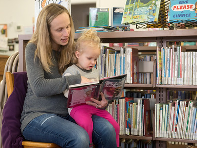 Globe/Roger Nomer Terryn Bollinger, Seneca, reads to her daughter Lakin, 2, on Thursday at the Seneca Public Library.
