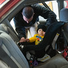 Globe/Roger Nomer<br /> Missouri Highway Patrol Sgt. John Lueckenhoff straps Preston Edgington, 9 months, into a car seat during Wednesday's car seat check at Fire Station #2. The Alliance of Southwest Missouri at Joplin firefighters partnered to help properly install car seats.