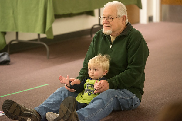 Globe/Roger Nomer<br /> Carl Johnson, Joplin, helps his grandson Logan, 13 months, clap along to the music on Tuesday at Movers and Shakers at the Joplin Public Library.