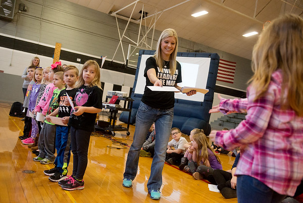 Globe/Roger Nomer<br /> Caroline Capehart hands out running awards to kindergarten students on Wednesday at Frontenac's Frank Layden Elementary.