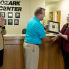 Globe/Roger Nomer<br /> As Freeman Health Systems CEO and President Paula Baker looks on, Adrian Hopper, veterans' representative for the State of Missouri division of workforce development, presents Mary Parrigon, executive director of Ozark Center, with the Flag of Freedom Award on Wednesday at Ozark Center. The award is from the Missouri Show Me Heroes initiative, and it honors Missouri businesses that have made an effort to hire military veterans.
