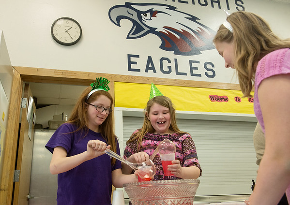 Globe/Roger Nomer<br /> Royal Heights fifth graders (from left) Grace Simon, Katelyn Young and Ellie Towe prepare refreshments during the 100th birthday celebration on Monday at Royal Heights Elementary.