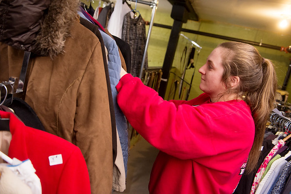 Brenna Swartz helps sort warm clothing at Watered Gardens on Tuesday afternoon.<br /> Globe | Roger Nomer