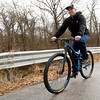 Blue's Bikes owner Mark Cox rides through Dover Park on Thursday morning.<br /> Globe | Laurie Sisk